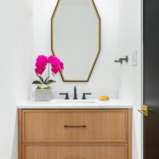 Cette image montre un WC et toilettes nordique avec des portes de placard en bois clair, un mur blanc, un sol en bois clair, un lavabo encastré, un plan de toilette blanc et meuble-lavabo suspendu.