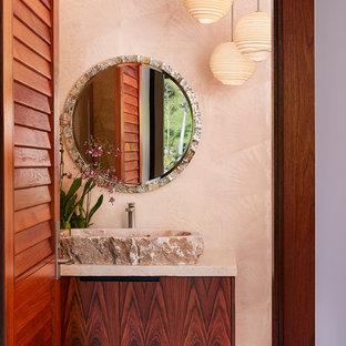 Inspiration för ett tropiskt toalett, med släta luckor, skåp i mellenmörkt trä, beige väggar, ett fristående handfat och granitbänkskiva