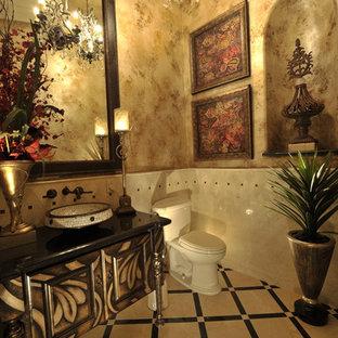 Cette photo montre un WC et toilettes éclectique avec un placard en trompe-l'oeil, un plan de toilette en marbre, un carrelage beige, un carrelage de pierre, un mur multicolore et un sol en marbre.