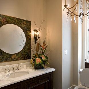 サンフランシスコのトロピカルスタイルのおしゃれなトイレ・洗面所 (アンダーカウンター洗面器、濃色木目調キャビネット、白い洗面カウンター) の写真