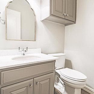 Ispirazione per un piccolo bagno di servizio chic con ante con bugna sagomata, ante grigie, WC a due pezzi, piastrelle grigie, piastrelle in gres porcellanato, pareti grigie, pavimento in ardesia, lavabo sottopiano e top in quarzo composito