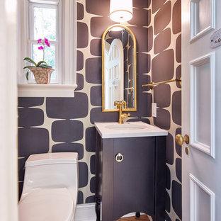 Klassisk inredning av ett litet vit vitt toalett, med möbel-liknande, svarta skåp, en toalettstol med hel cisternkåpa, svarta väggar, ett undermonterad handfat, bänkskiva i kvarts, mellanmörkt trägolv och brunt golv