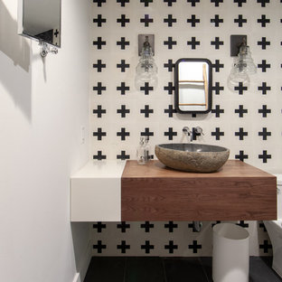 Inspiration for a farmhouse cloakroom in Charlotte with medium wood cabinets, black and white tiles, white walls, slate flooring, a vessel sink, wooden worktops, grey floors and brown worktops.