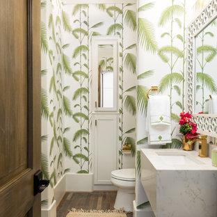 Idée de décoration pour un WC et toilettes ethnique avec des portes de placard blanches, un WC à poser, un mur multicolore, un sol en bois brun, un plan de toilette en quartz modifié, un sol marron et un lavabo encastré.