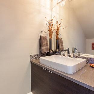 Modelo de aseo moderno, pequeño, con armarios con paneles lisos, puertas de armario de madera en tonos medios, sanitario de una pieza, baldosas y/o azulejos grises, baldosas y/o azulejos en mosaico, paredes blancas, suelo vinílico, lavabo sobreencimera, encimera de terrazo y encimeras grises