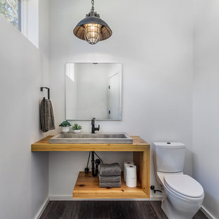 Photo of a rustic cloakroom in Other with open cabinets, light wood cabinets, a two-piece toilet, white walls, dark hardwood flooring, a vessel sink, wooden worktops, brown floors and brown worktops.