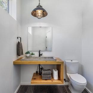 Imagen de aseo rústico con armarios abiertos, puertas de armario de madera clara, sanitario de dos piezas, paredes blancas, suelo de madera oscura, lavabo sobreencimera, encimera de madera, suelo marrón y encimeras marrones