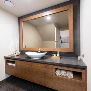 Неиссякаемый источник вдохновения для домашнего уюта: туалет среднего размера в современном стиле с фасадами островного типа, фасадами цвета дерева среднего тона, раздельным унитазом, черной плиткой, керамогранитной плиткой, белыми стенами, полом из керамогранита, настольной раковиной, столешницей из искусственного кварца, черным полом и черной столешницей