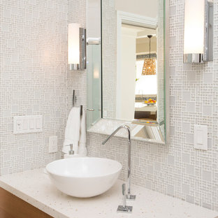 Inspiration for a beach style white tile powder room remodel in Miami with flat-panel cabinets, medium tone wood cabinets, white walls, a vessel sink and white countertops