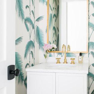 Esempio di un bagno di servizio costiero con ante in stile shaker, ante bianche, pareti multicolore, lavabo sottopiano e top bianco