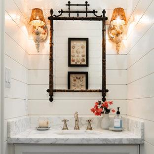 ダラスのビーチスタイルのおしゃれなトイレ・洗面所 (インセット扉のキャビネット、グレーのキャビネット、白い壁、アンダーカウンター洗面器、白い洗面カウンター、造り付け洗面台、塗装板張りの壁) の写真