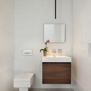 Immagine di un bagno di servizio minimalista di medie dimensioni con ante lisce, ante in legno bruno, WC sospeso, piastrelle grigie, piastrelle bianche, piastrelle in gres porcellanato, pareti bianche, pavimento in gres porcellanato, lavabo integrato, top in superficie solida e pavimento beige