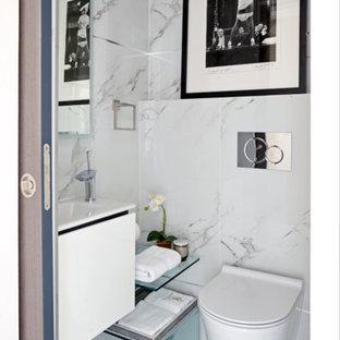 Diseño de aseo moderno, pequeño, con armarios con paneles lisos, puertas de armario blancas, sanitario de pared, baldosas y/o azulejos grises, baldosas y/o azulejos blancos, baldosas y/o azulejos de mármol, paredes blancas, lavabo suspendido y suelo blanco