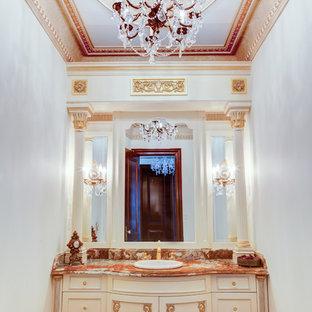Réalisation d'un très grand WC et toilettes victorien avec un placard avec porte à panneau encastré, des portes de placard beiges, un WC suspendu, un carrelage beige, un mur beige, un sol en bois clair, un lavabo posé, un plan de toilette en granite, un sol multicolore et un plan de toilette multicolore.