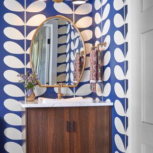 Ejemplo de aseo retro con armarios tipo mueble, puertas de armario de madera en tonos medios, paredes multicolor, suelo de madera clara, lavabo encastrado y encimeras blancas