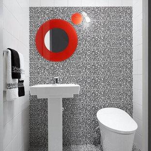 Пример оригинального дизайна: большой туалет в стиле модернизм с унитазом-моноблоком, черно-белой плиткой, белой плиткой, керамической плиткой, белыми стенами, полом из керамической плитки и раковиной с пьедесталом
