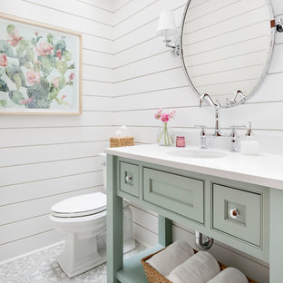 Country powder room in Seattle with beaded inset cabinets, green cabinets, a two-piece toilet, white walls, an undermount sink, grey floor and white benchtops.