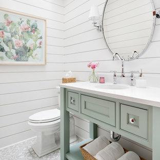 Modelo de aseo de estilo de casa de campo con armarios con rebordes decorativos, puertas de armario verdes, sanitario de dos piezas, paredes blancas, lavabo bajoencimera, suelo gris y encimeras blancas