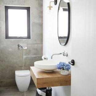 Свежая идея для дизайна: туалет в современном стиле с фасадами островного типа, светлыми деревянными фасадами, инсталляцией, серой плиткой, цементной плиткой, полом из цементной плитки, столешницей из ламината и серым полом - отличное фото интерьера