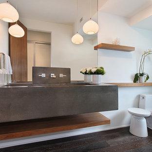 Modelo de aseo contemporáneo con encimera de cemento, paredes blancas, lavabo de seno grande y encimeras grises