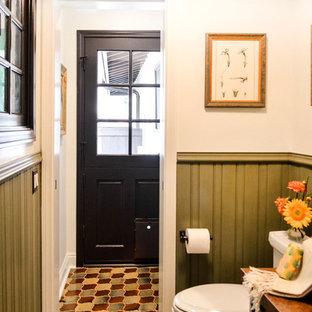 Пример оригинального дизайна: маленький туалет в средиземноморском стиле с фасадами островного типа, темными деревянными фасадами, унитазом-моноблоком, зеленой плиткой, белыми стенами, полом из керамической плитки, настольной раковиной, столешницей из меди, разноцветным полом и коричневой столешницей