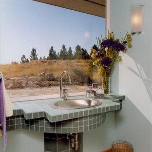 Exemple d'un WC et toilettes chic de taille moyenne avec un carrelage vert, des carreaux de céramique, un mur bleu, un sol en bois clair, un lavabo posé, un plan de toilette en carrelage et un plan de toilette vert.