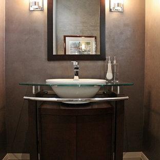Aménagement d'un WC et toilettes contemporain de taille moyenne avec un lavabo posé, un placard en trompe-l'oeil, un plan de toilette en verre, un WC séparé, un mur noir, un sol en carrelage de céramique, un carrelage gris et des portes de placard en bois sombre.
