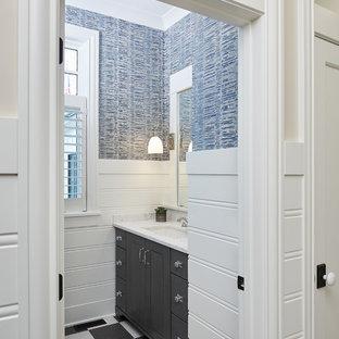 Exemple d'un WC et toilettes nature avec un placard avec porte à panneau encastré, des portes de placard noires, un mur bleu, un sol en carrelage de terre cuite, un lavabo encastré, un plan de toilette en quartz modifié et un sol noir.