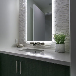 Exemple d'un WC et toilettes tendance de taille moyenne avec un placard à porte plane, des portes de placard en bois sombre, un carrelage blanc, des carreaux de porcelaine, un mur blanc, un sol en carrelage de porcelaine, un lavabo encastré et un plan de toilette en quartz modifié.