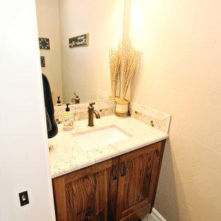 Cette photo montre un petit WC et toilettes chic avec un placard avec porte à panneau surélevé, des portes de placard en bois brun, un WC séparé, un carrelage beige, des plaques de verre, un mur beige, un sol en carrelage de céramique, un lavabo encastré, un plan de toilette en granite et un sol beige.