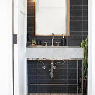 На фото: маленькие туалеты в современном стиле с унитазом-моноблоком, черной плиткой, цементной плиткой, черными стенами, полом из цементной плитки, раковиной с пьедесталом, мраморной столешницей и разноцветным полом