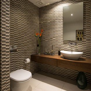 This is an example of a large contemporary cloakroom in Auckland with flat-panel cabinets, a one-piece toilet, multi-coloured tiles, multi-coloured walls, porcelain flooring, a vessel sink, wooden worktops, dark wood cabinets, brown worktops, mosaic tiles and beige floors.