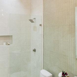 На фото: с высоким бюджетом туалеты среднего размера в современном стиле с фасадами цвета дерева среднего тона, бежевой плиткой, стеклянной плиткой, настольной раковиной, столешницей из дерева, унитазом-моноблоком и коричневой столешницей