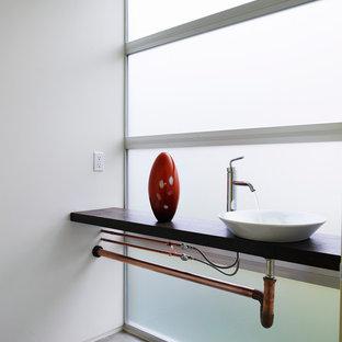 Ejemplo de aseo industrial con lavabo sobreencimera, paredes blancas y suelo de cemento