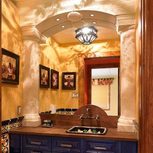 Свежая идея для дизайна: туалет с накладной раковиной, фасадами с выступающей филенкой, синими фасадами, столешницей из дерева, разноцветной плиткой и коричневой столешницей - отличное фото интерьера