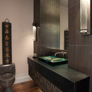 Foto de aseo asiático, pequeño, con lavabo sobreencimera, puertas de armario grises, encimera de granito, paredes beige y suelo de madera en tonos medios