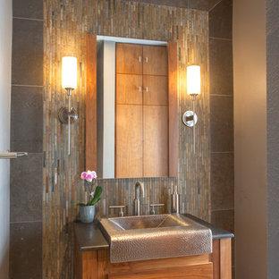 На фото: туалет среднего размера в стиле рустика с фасадами островного типа, фасадами цвета дерева среднего тона, серой плиткой, серыми стенами, полом из известняка, плиткой из сланца, раковиной с несколькими смесителями, мраморной столешницей и бежевым полом с