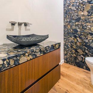 На фото: туалет среднего размера в современном стиле с плоскими фасадами, фасадами цвета дерева среднего тона, разноцветной плиткой, плиткой из листового камня, белыми стенами, паркетным полом среднего тона, настольной раковиной, столешницей из гранита, коричневым полом и разноцветной столешницей с