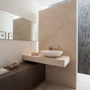 Modelo de aseo actual, extra grande, con lavabo sobreencimera, armarios tipo mueble, puertas de armario de madera en tonos medios, encimera de piedra caliza, baldosas y/o azulejos beige, azulejos en listel, paredes blancas, suelo de travertino y encimeras beige