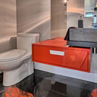 Kleine Moderne Gästetoilette mit flächenbündigen Schrankfronten, roten Schränken, Toilette mit Aufsatzspülkasten, grauer Wandfarbe, Betonboden, Wandwaschbecken, Mineralwerkstoff-Waschtisch und rotem Boden in Montreal