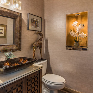Kleine Klassische Gästetoilette mit verzierten Schränken, hellbraunen Holzschränken, Toilette mit Aufsatzspülkasten, braunen Fliesen, Mosaikfliesen, braunem Holzboden, Aufsatzwaschbecken, Travertin-Waschtisch und braunem Boden in Sonstige