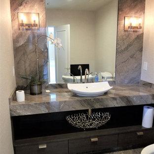 Стильный дизайн: маленький туалет в современном стиле с плоскими фасадами, темными деревянными фасадами, унитазом-моноблоком, бежевыми стенами, полом из известняка, настольной раковиной, столешницей из известняка, разноцветным полом, разноцветной столешницей и встроенной тумбой - последний тренд