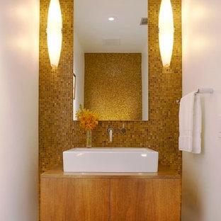 Moderne Gästetoilette mit Aufsatzwaschbecken, flächenbündigen Schrankfronten, hellbraunen Holzschränken, Waschtisch aus Holz, gelben Fliesen, Mosaikfliesen, Porzellan-Bodenfliesen, gelber Wandfarbe und brauner Waschtischplatte in Los Angeles