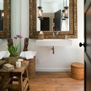 На фото: туалеты среднего размера в средиземноморском стиле с подвесной раковиной, белыми стенами и паркетным полом среднего тона