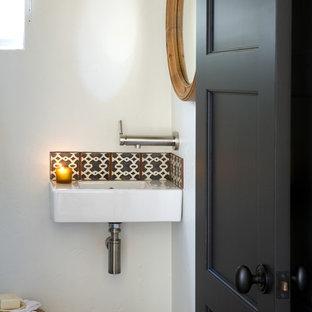 На фото: маленький туалет в средиземноморском стиле с подвесной раковиной, разноцветной плиткой, керамической плиткой и белыми стенами