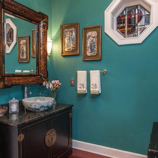 Modelo de aseo de estilo zen, de tamaño medio, con lavabo sobreencimera, armarios tipo mueble, puertas de armario negras, encimera de granito, paredes azules y suelo de madera en tonos medios