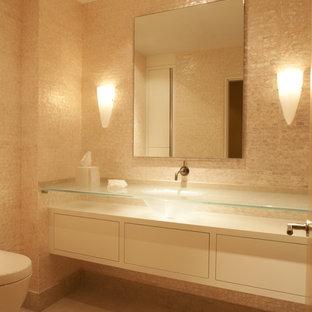 Diseño de aseo contemporáneo con encimera de vidrio, lavabo integrado y baldosas y/o azulejos beige