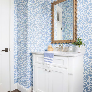 Photo of a beach style powder room in Minneapolis with recessed-panel cabinets, white cabinets, multi-coloured walls, dark hardwood floors, an undermount sink, marble benchtops and grey benchtops.