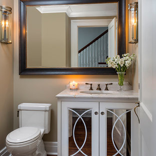 Пример оригинального дизайна: маленький туалет в классическом стиле с белыми фасадами, унитазом-моноблоком, бежевыми стенами, паркетным полом среднего тона, врезной раковиной, столешницей из кварцита, стеклянными фасадами и белой столешницей