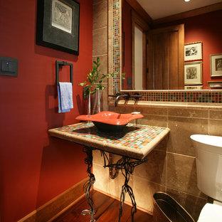 Modelo de aseo clásico, pequeño, con sanitario de dos piezas, baldosas y/o azulejos azules, baldosas y/o azulejos verdes, baldosas y/o azulejos naranja, baldosas y/o azulejos rojos, baldosas y/o azulejos beige, baldosas y/o azulejos multicolor, baldosas y/o azulejos en mosaico, paredes rojas, suelo de madera oscura, lavabo sobreencimera y encimera de azulejos